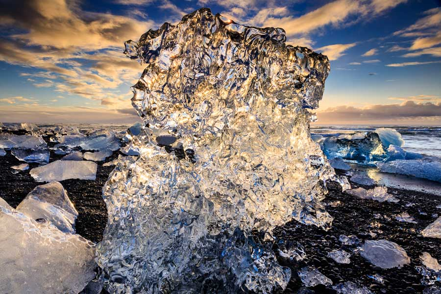 The morning sun is shining through a growler on the black pebble beach at Jökulssarlon