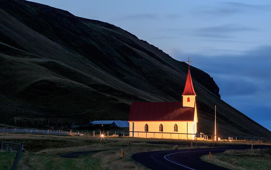 Reyniskirkja lit up at night against the obligatory mountain backdrop