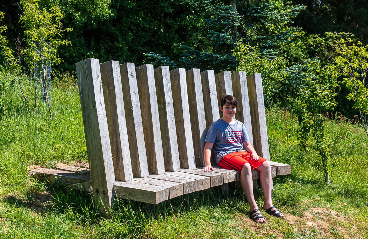 Eric sitting on the bench looking out over the meadow